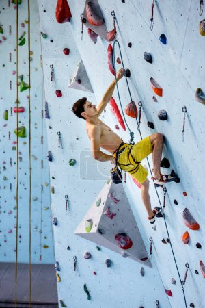 Climbing gym. Sport training. Strong athlete on a climbing wall, olympic sports discipline.