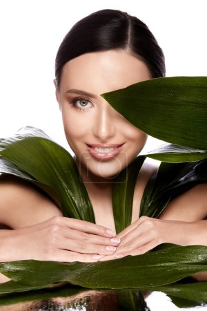 Photo for Beautiful and natural young woman posing with green leaves at grey background, skin care concept, hydrated skin - Royalty Free Image