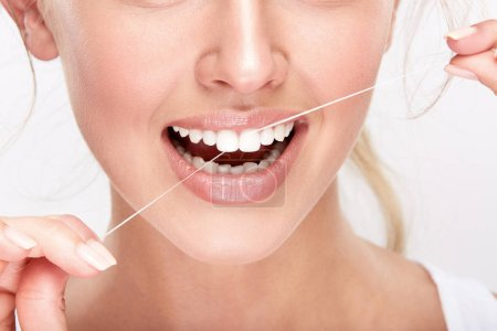 beautiful smiling woman with white teeth using dental floss, dentistry concept