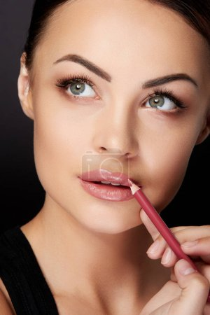 beauty concept, young woman painting lips with red lipliner, black background