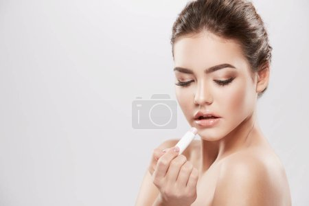 beautiful and natural young woman with naked shoulders using lip balm, skin care concept