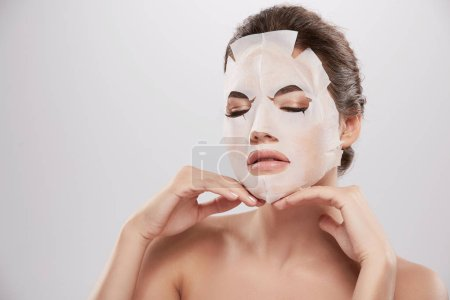 beautiful and natural young woman applying facial mask, skin care concept, skin treatment, hydrating skin mask