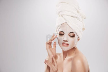 beautiful and natural young woman with turban towel on head applying facial mask, skin care concept, skin treatment, hydrating skin mask
