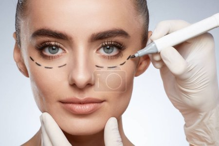 beauty portrait of attractive woman, plastic surgery concept. Model with puncture lines on face, hands in gloves drawing