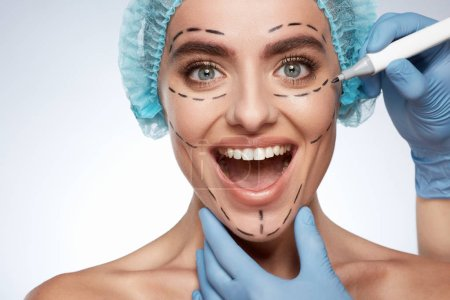 beauty portrait of smiling woman, plastic surgery concept. Model in blue cap with puncture lines on face, hands in blue gloves drawing