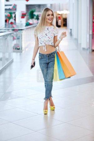 Photo pour Belle jeune femme blonde avec des sacs colorés dans le centre commercial - image libre de droit