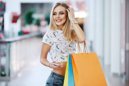 Photo for Beautiful blonde young woman with colorful shopping bags in shopping mall - Royalty Free Image