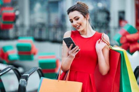 Photo pour Belle brune jeune femme avec des sacs à provisions colorés en utilisant le téléphone mobile, concept de magasinage en ligne - image libre de droit
