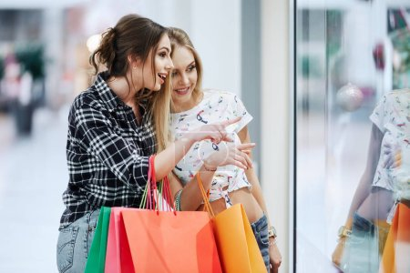 Photo for Pretty young women with colorful shopping bags looking at shop window in shopping mall - Royalty Free Image