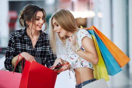 Photo for Pretty young women with colorful shopping bags at shopping mall - Royalty Free Image