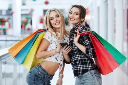 Photo for Pretty young women posing with colorful shopping bags at shopping mall - Royalty Free Image
