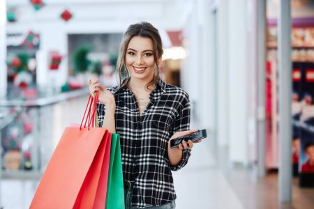 beautiful brunette young woman with colorful shopping bags using mobile phone, online shopping concept