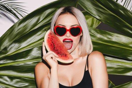 Photo pour Fille chaude aux cheveux blonds portant un maillot de bain noir et des lunettes de soleil debout sur le fond de feuilles de palmier posant avec une tranche de pastèque et des lèvres rouges, lécher - image libre de droit