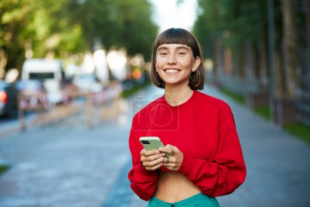Photo for Pretty girl in red holding phone on street, cute millenial woman in red stylish sweater having smartphone and looking to camera with smile - Royalty Free Image