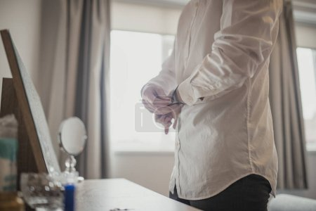 Photo for Side view of an unrecognisable person standing at a dresser table putting a watch on. - Royalty Free Image