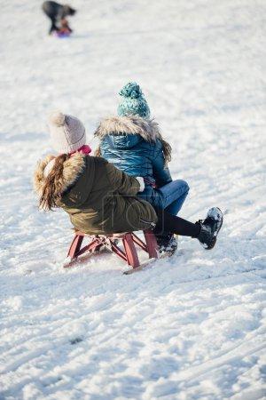 Photo pour Vue arrière de deux filles qui descendent ensemble une colline dans la neige . - image libre de droit