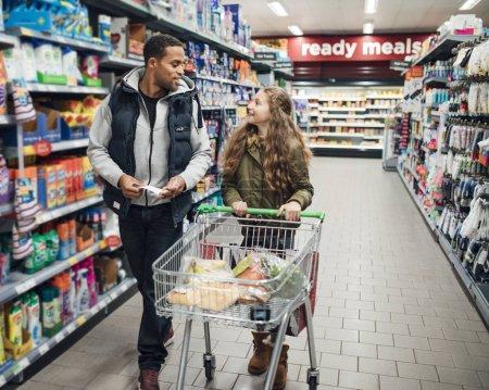 Photo pour Petite fille et son père marchent dans une allée au supermarché avec un chariot et une liste de courses . - image libre de droit