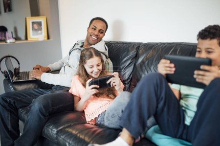 Photo for Siblings are playing together on handheld consoles on the sofa at home while their father is using a laptop next to them. - Royalty Free Image