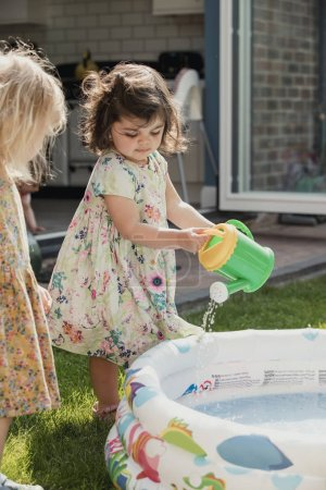 Photo for Side view of two little girls standing next to an inflateable pool. One little girl is using a toy watering can to pour water into the pool. - Royalty Free Image