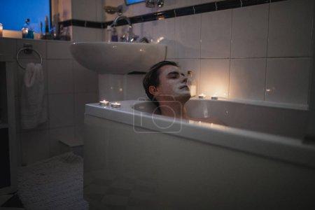 Photo pour Jeune homme est de se détendre dans le bain avec un masque sur et bougies allumées autour de lui. - image libre de droit