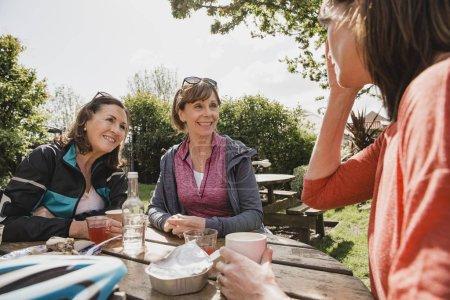 Photo pour Trois femmes profitent de rafraîchissements dans un café ensemble après une balade à vélo difficile. - image libre de droit