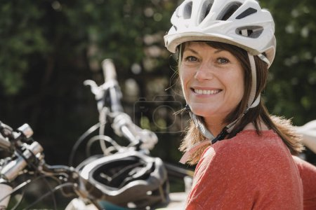 Photo for Headshot of a mature female wearing a cycling helmet and looking at the camera and smiling. - Royalty Free Image