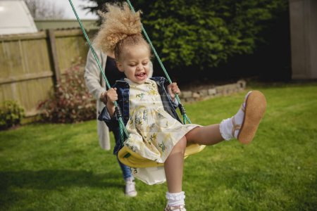 Photo for Little girl having fun while being pushed on a swing by her mother. - Royalty Free Image