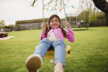 Photo for Little girl playing outside on a swing while her her mother helps and pushes her. She is having fun and enjoying herself. - Royalty Free Image