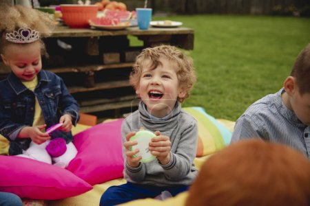Photo for Excited little boy sitting outdoors with his friends surrounding him. He is amazed by the slime in a pot which he is holding. - Royalty Free Image