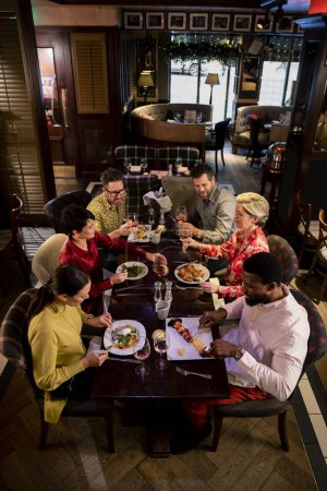 Photo for Small group of friends enjoying a meal in a restaurant. They are sitting at a table as they eat their food. - Royalty Free Image