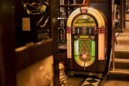 Photo pour Jukebox rétro dans le coin d'un restaurant par un ensemble d'escaliers. - image libre de droit