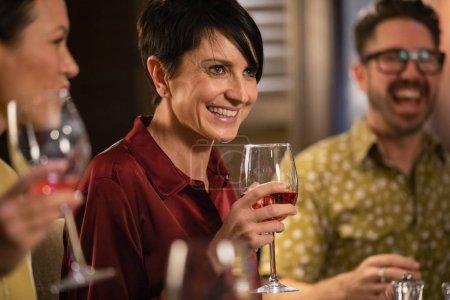 Photo pour Gros plan d'une femme mûre tenant un verre de vin de rose. Elle sourit et parle avec des amis dans un restaurant . - image libre de droit