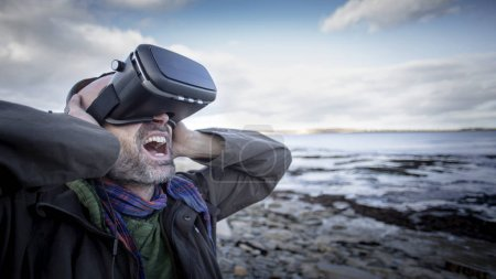 Photo for A front-view shot of a mature caucasian man wearing a virtual reality headset while standing on a beach in the United Kingdom, he has his arms raised is expressing anger. - Royalty Free Image