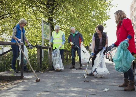 Photo pour Un groupe de cinq personnes participant ensemble au nettoyage d'une ville . - image libre de droit