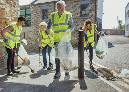 Photo pour Un groupe de cinq personnes portant des vestes de haute visibilité participant à un nettoyage de la ville ensemble . - image libre de droit