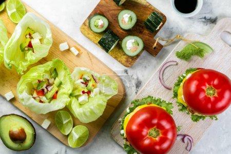 Photo pour Choix d'options de repas faibles en glucides - hamburger, taco, sushi, vue sur le dessus - image libre de droit