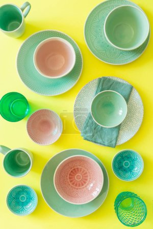 Photo for Selection of colorful tableware on bright yellow background, top view - Royalty Free Image