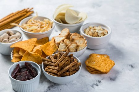 Photo for Salty beer snacks in whit bowls, copy space - Royalty Free Image