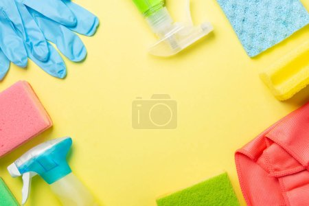 Photo for Cleaning concept - cleaning supplies, gloves, bottles on pastel yellow background, copy space - Royalty Free Image