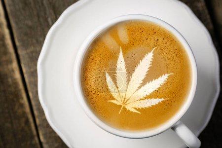 Photo for Cannabis coffee - marijuana leaf on coffee foam, rustic wood background - Royalty Free Image