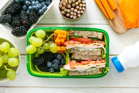 Photo for Back to school concept - lunch box with juice, apple and banana, copy space - Royalty Free Image