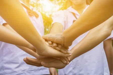 Photo pour Les jeunes joignent les mains à l'extérieur comme signe d'un bon travail d'équipe - image libre de droit