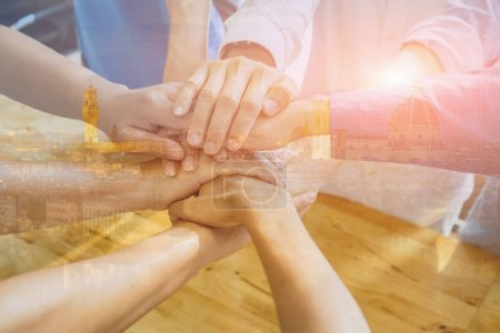Business team joining hands together in office as sign of good teamwork