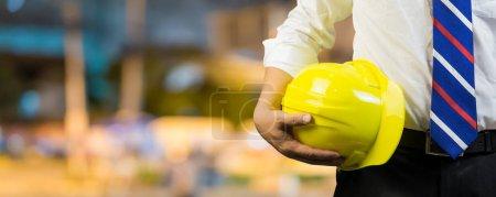 Photo pour Homme ingénieur tenant dans la main casque jaune à l'extérieur - image libre de droit