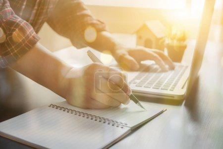 Photo pour Homme d'affaires travaillant sur ordinateur portable et l'écriture dans le bureau - image libre de droit