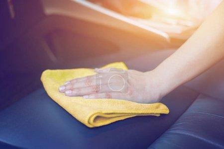 Photo pour Main avec tissu microfibre jaune nettoyage siège auto en cuir - image libre de droit