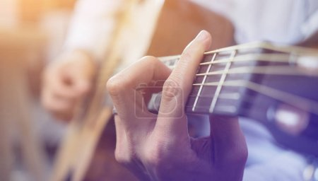 Photo pour Jeunes hommes pratiquant la guitare leçon - image libre de droit