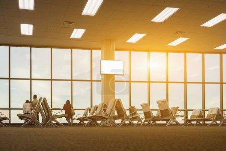 passenger seats in departure lounge at airport terminal