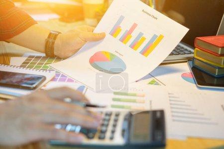 Photo pour Image recadrée de Businessman analysant les graphiques d'investissement avec calculatrice dans le bureau - image libre de droit