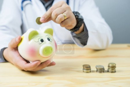 Photo pour Image recadrée du médecin mettant de la monnaie dans une tirelire à l'hôpital - image libre de droit